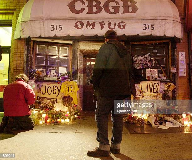 Mourners stop by punk rock club CBGB's in New York April 18 2001 to lay flowers and pay their respects at a shrine to the late Joey Ramone of the...