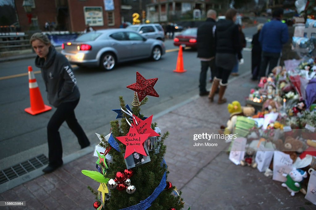 Mourners visit a streetside memorial for 20 children and 6 adults who were killed at Sandy Hook Elementary School on December 20, 2012 in Newtown, Connecticut. Six funeral services were held Thursday in the Newtown area for students and teachers slain in the attack.