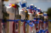Mourners visit the 12 crosses erected near the Aurora Municipal Building July 20 2013 in Aurora Colorado A remembrance ceremony marks the one oneyear...