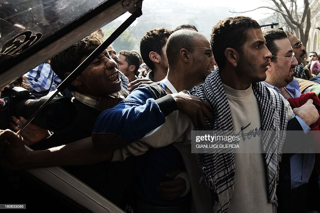 Mourners wait to load the coffins of killed Egyptian activists Amro Saad and Mohammed al-Guindi during their funeral outside Omar Makram Mosque in Cairo's Tahrir Square on February 4, 2013. Saad died in clashes during anti-government protests on February 1, while Guindi, 28, went missing last month after joining protests demanding change on the second anniversary of Egypt's uprising against former president Hosni Mubarak and then slipped into a coma following days in police custody, according to the health ministry and his party.