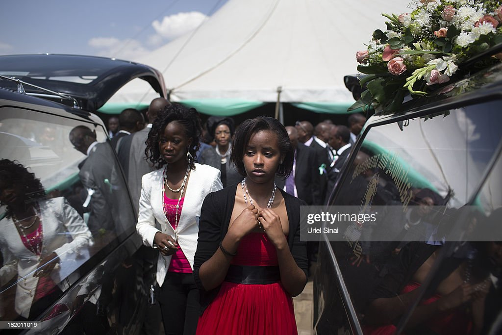 Mourners walk between hearses after a funeral service for Kenyan President Uhuru Kenyatta's nephew Mbugua Mwangi and his fiancee Rosemary Wahito who were killed at the the Westgate Mall terrorist attack, on September 27, 2013 in Nairobi, Kenya. The country is observing three days of national mourning as security forces begin the task of clearing and securing the Westgate shopping mall following a four-day siege by militants.