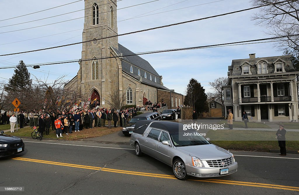 Mourners watch as a hearse departs the funeral of Benjamin Wheeler, 6, at the Trinity Episcopal Church on December 20, 2012 in Newtown, Connecticut. Benjamin, a member of Tiger Scout Den 6, was killed when 20 children and six adults were massacred at Sandy Hook Elementary School last Friday.