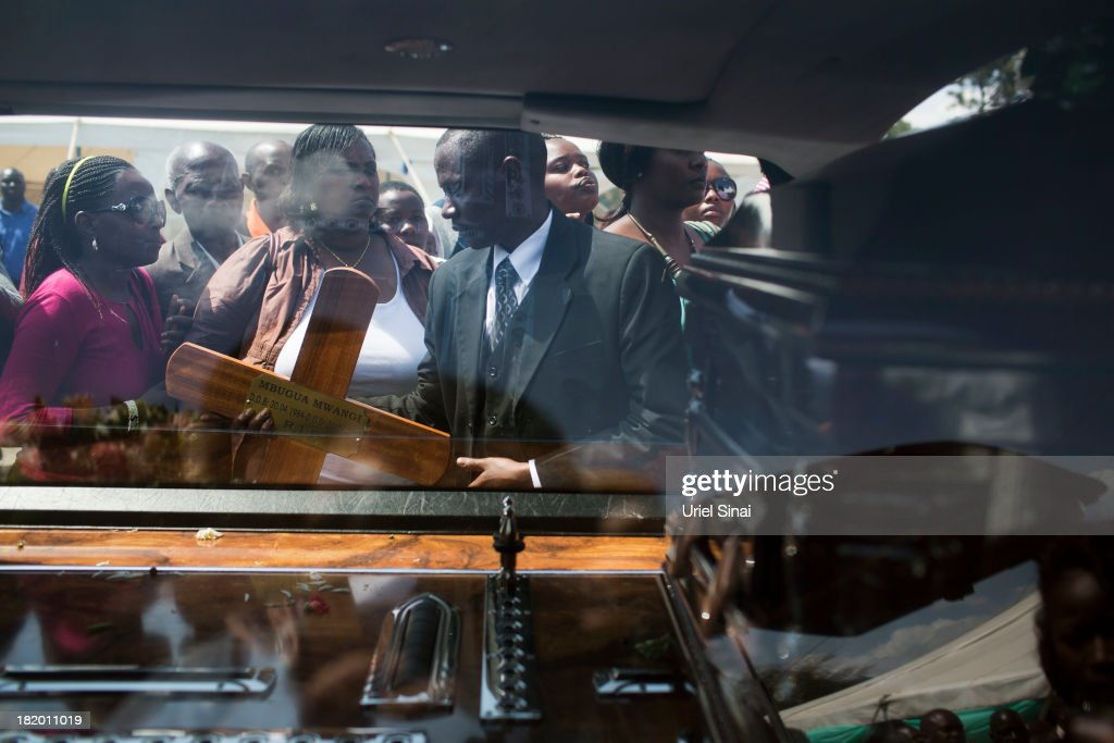 Mourners watch as the coffin of President Uhuru Kenyatta's nephew Mbugua Mwangi is loaded into hearse after a funeral service for him and his fiancee Rosemary Wahito who were killed at the the Westgate Mall terrorist attack, on September 27, 2013 in Nairobi, Kenya. The country is observing three days of national mourning as security forces begin the task of clearing and securing the Westgate shopping mall following a four-day siege by militants.