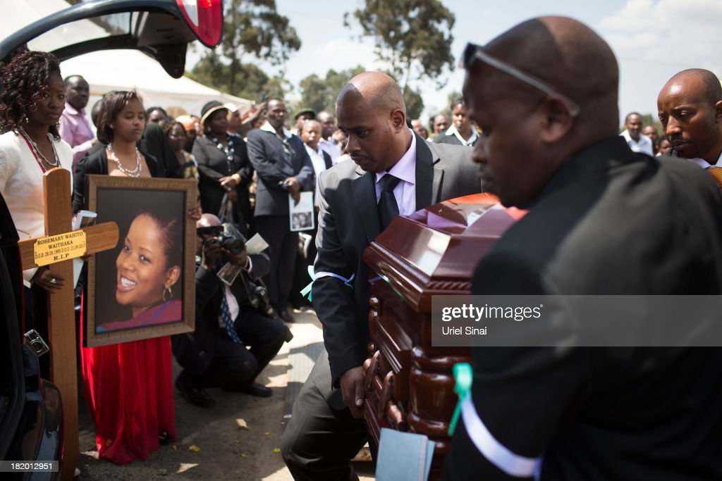 Mourners watch as the coffin of Rosemary Wahito is loaded into a hearse on September 27, 2013 in Nairobi, Kenya. Wahito was killed with her fiancee, President Uhuru Kenyatta's nephew, Mbugua Mwangi at the Westgate Mall terrorist attack. The country is observing three days of national mourning as security forces begin the task of clearing and securing the Westgate shopping mall following a four-day siege by militants.