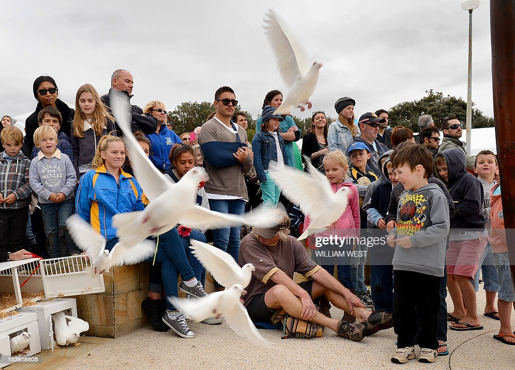 Mourners watch doves released after a ceremony to commemorate the 10th anniversary of the 2002 Bali attacks, at a memorial dedicated to Australians killed in the attacks, at Coogee Beach in Sydney on October 12, 2012. Survivors and relatives of the dead flocked to emotional Bali bombing ceremonies across Australia on October 12, with Foreign Minister Bob Carr praising the nation's mature response to the atrocity. AFP PHOTO/William WEST
