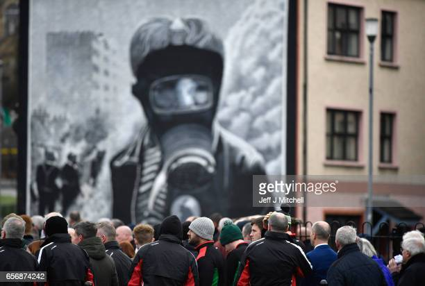 Mourners watch Martin McGuinness' funeral on a large screen at Free Derry Corner on March 23 2017 in Londonderry Northern Ireland The funeral is held...
