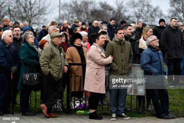 Mourners watch Martin McGuinness' funeral on a large screen in the Bogside on March 23 2017 in Londonderry Northern Ireland The funeral is held for...