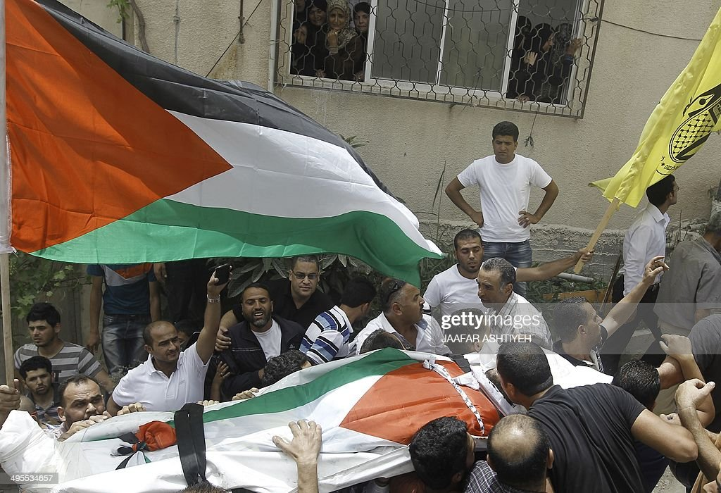 Mourners watch on as Palestinians carry the body of Alaa Awdeh, draped in the Palestinian flag, during his funeral procession in the West Bank village of Hawara on June 4, 2014, after he was killed at the Tapuach junction in the northern West Bank late on June 2. Israeli security forces killed Awdeh after he shot and wounded a border guard in the northern West Bank, the army said.