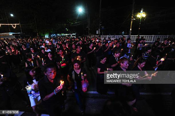 Mourners wearing black hold candles to pay respects to the late Thai King Bhumibol Adulyadej in the southern province of Narathiwat on October 14...