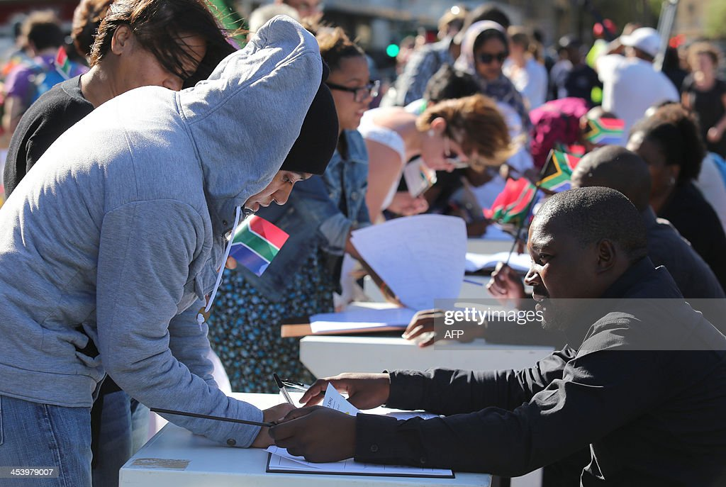 Mourners write in condolence books as they gather to honour late South African former president Nelson Mandela at an inter-faith service on December 6, 2013, held at the Grand Parade in Cape Town, where Mandela made his first speech as a free man in 1990. Mandela, the revered icon of the anti-apartheid struggle in South Africa and one of the towering political figures of the 20th century, died in Johannesburg on December 5 at age 95. Mandela, who was elected South Africa's first black president after spending nearly three decades in prison, had been receiving treatment for a lung infection at his Johannesburg home since September, after three months in hospital in a critical state.