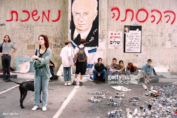 Mourning Israelis stand next to a memorial on November 7 1995 at the site of Israeli Prime Minister Yitzhak Rabin's assassination on November 4 Tens...