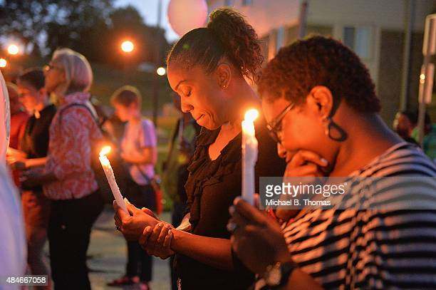 Mourning participants pause in a moment of prayer at the Michael Brown Jr memorial during a candlelight vigil held in honor of Jamyla Bolden on...