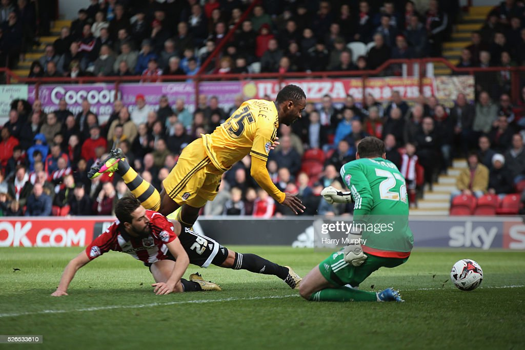 Moussa Dembele of Fulham is tackled by Yoann Barbet of Brentford during the Sky Bet Championship match between Brentford and Fulham at Griffin Park on April 30, 2016 in Brentford, United Kingdom.