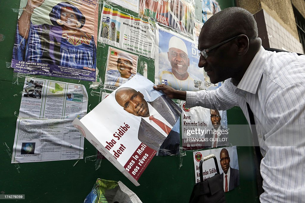 Moussa Gory, responsable in France for the electoral campaign of Malian presidential candidate Konimba Sidibe, holds a poster displaying Sidibe at the entrance of the Bara centre on July 23, 2013 in Montreuil, a Paris suburb. Mali is hoping against the odds for credible July 28 presidential elections but crucial barriers to an acceptable voter turnout and the ever-present threat of terrorist attacks are casting a long shadow over preparations. The polls are seen as vital to reuniting the country after a March 2012 military coup and a sweeping offensive by Islamist rebels who captured the entire north before being flushed out by French and African troops. AFP PHOTO / FRANCOIS GUILLOT