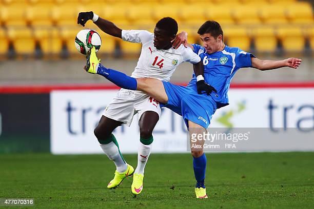 Moussa Kone of Senegal is challenged by Akramjon Komilov of Uzbekistan during the FIFA U20 World Cup New Zealand 2015 Quarter Final match between...