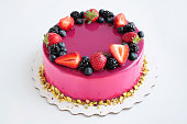 Birthday mousse cake with pink mirror glaze and with berries, pistachios. Picture for a menu or a confectionery catalog.