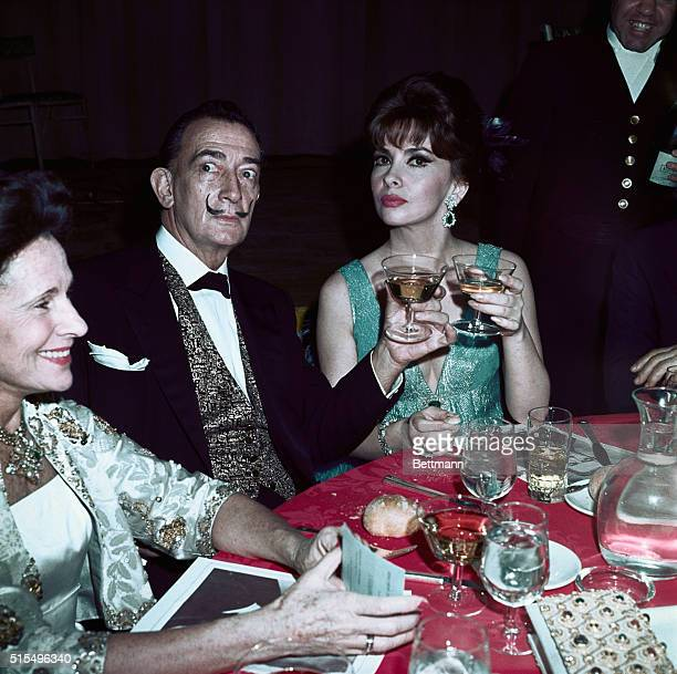Moustached artist Salvador Dali and lovely Gina Lollobrigida raise glasses together here at a party following the premier of The Sound of Music held...