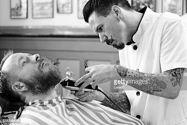 moustached barber trimming a client's beard
