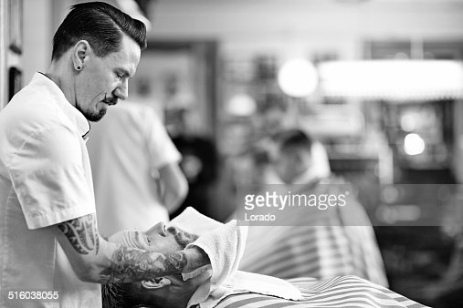 moustached barber working on client