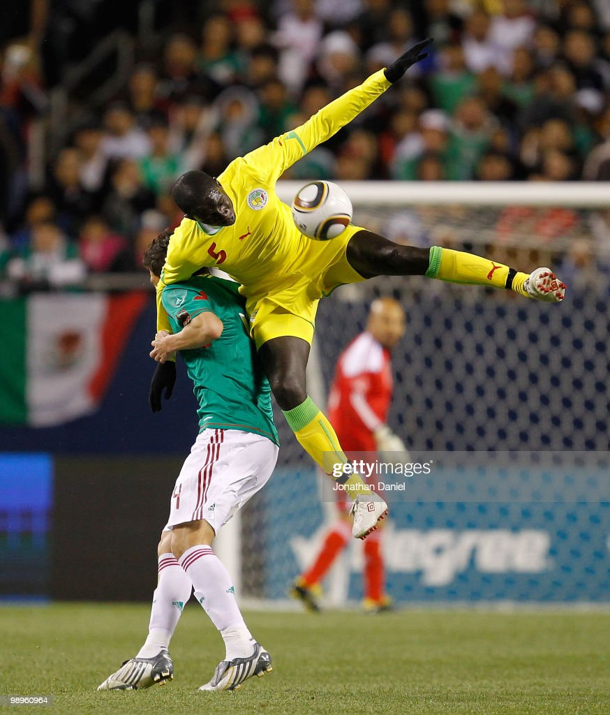 Moustapha Cisse of Senegal leaps for the ball and lands on the back of Hector Moreno of Mexico during an international friendly at Soldier Field on...