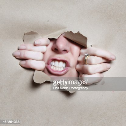 Mouth Nose and Hands Breaking through Brown Paper