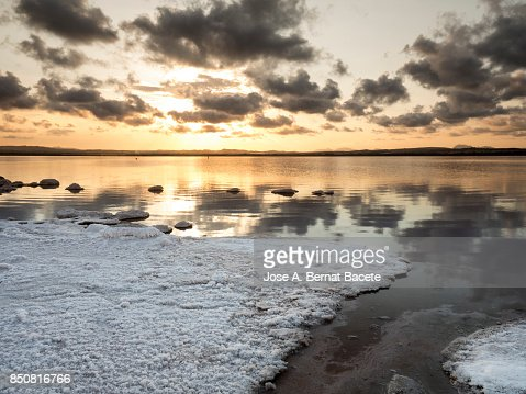 sunrise with clouds over water orange sunset with high clouds over a lake of calm water with
