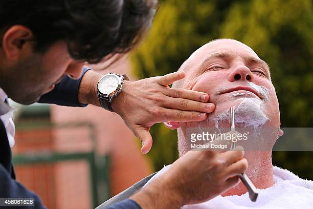 Movember professional barber France Khamees shaves down horse trainer Peter Moody at Peter Moody Stables at Caulfield Racecourse on October 30 2014...