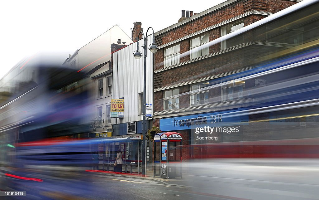 Movement from two passenger buses is seen as they drive past a Co-Operative Bank Plc branch, a unit of Co-Operative Group Ltd., in Leeds, U.K., on Wednesday, Sept. 25, 2013. The parent of Co-operative Bank, which is seeking capital after losses, may avoid being forced to rescue the lender thanks to an accord it struck with regulators last year, according to bondholders. Photographer: Paul Thomas/Bloomberg via Getty Images