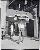A mover carrying a chair on his head on a moving day in New York City