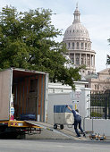 A mover rolls a cart of PresidentElect Bush's possessions into a United moving van outside the Governor's Mansion in Austin