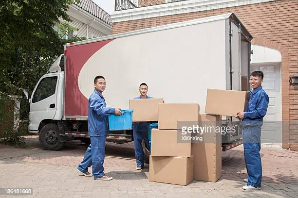 Movers unloading a moving van, many stacked cardboard boxes
