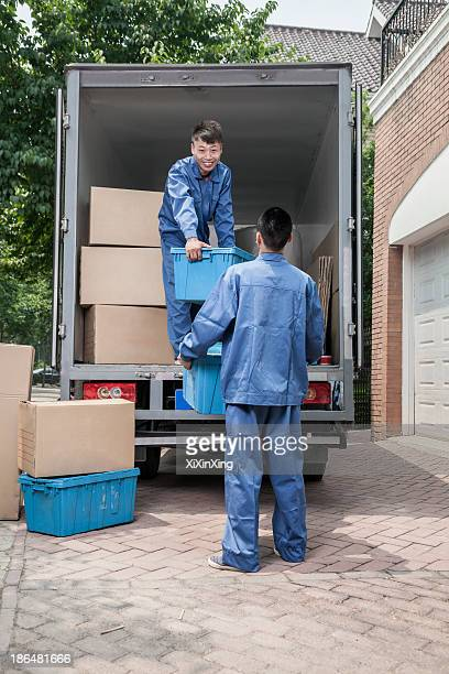 Movers unloading a moving van, passing a cardboard box
