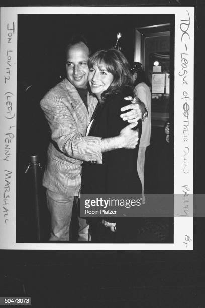 Movie dir/actress Penny Marshall getting hugged by actor Jon Lovitz at party for the premiere of her film A League of Their Own at Tavern on the...