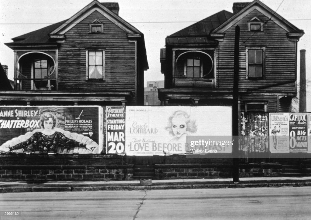 Movie posters, including one of Anne Shirley in 'Chatterbox' and another of Carole Lombard in 'Love Before Breakfast,' on a brick wall in front of wooden houses in Atlanta, Georgia.