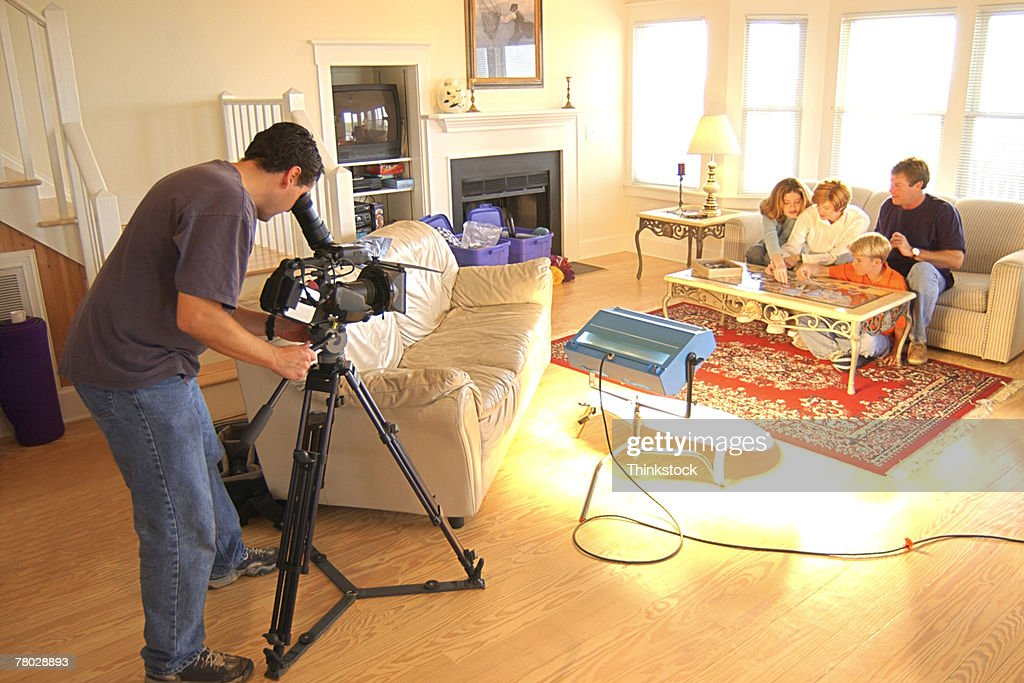 A movie production with the camera man using a tripod to videotape a family scene in a living room. : Stock Photo