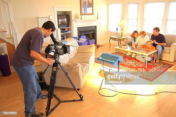 A movie production with the camera man using a tripod to videotape a family scene in a living room.