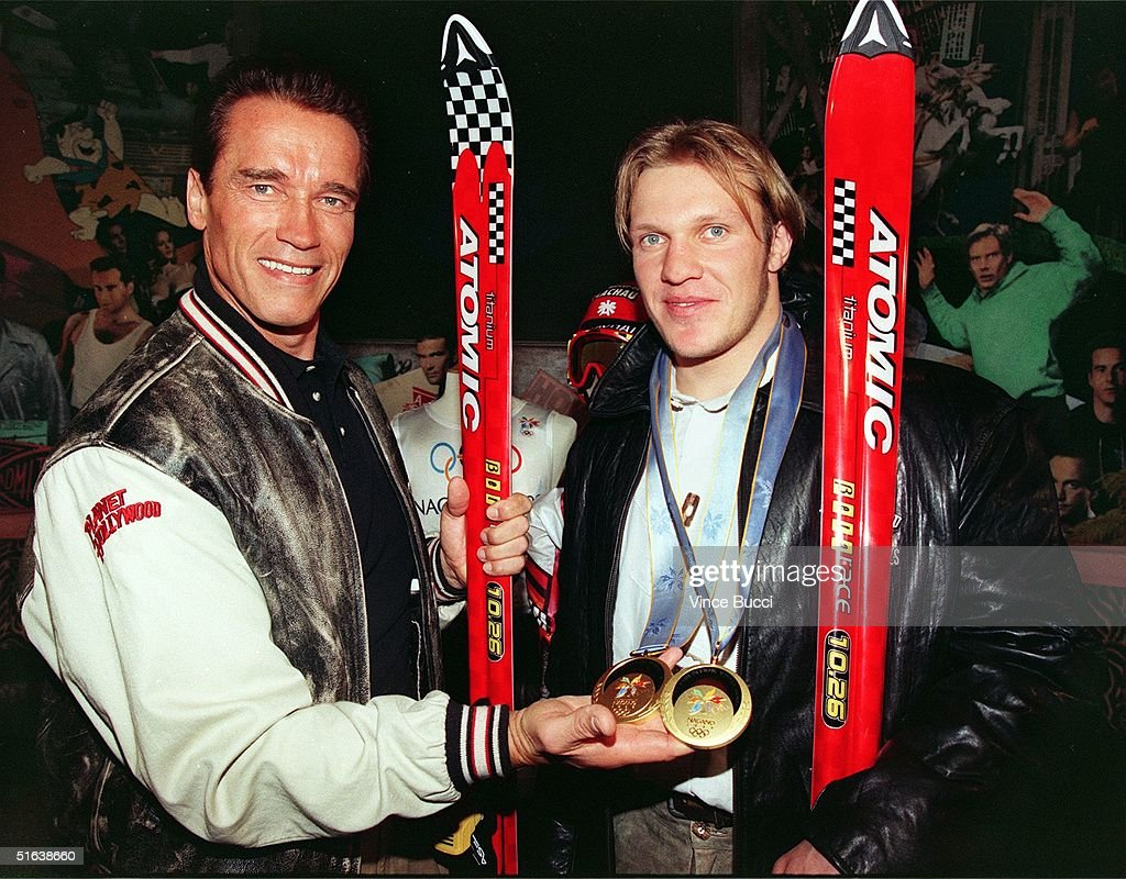 Movie star Arnold Schwarzenegger holds the two gold medals won by Olympic skier Hermann Maier at the Nagano Games as the two famous Austrians met 23...