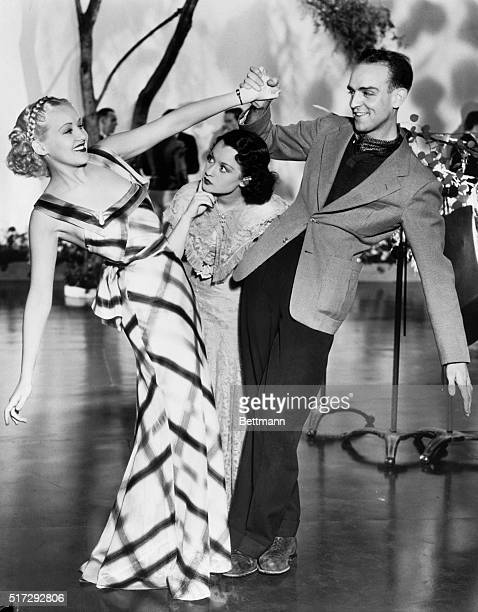 Movie star Betty Grable dances with choreographer Hermes Pan on a movie set Actress Evelyn Poe tries to break in between the pair