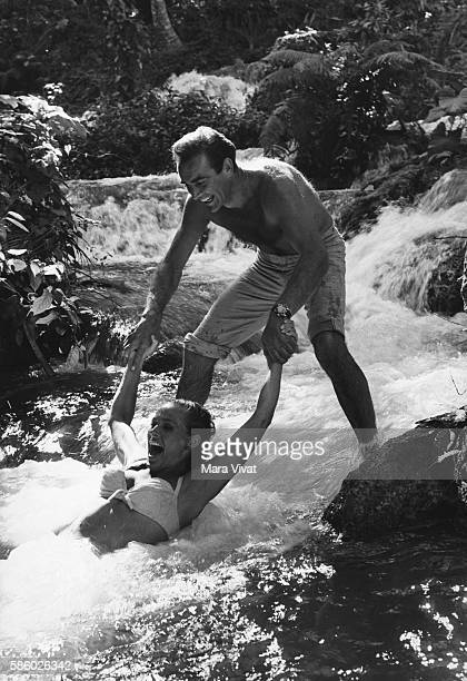 Movie stars Sean Connery and Ursula Andress play in a cascading river during the filming of the James Bond movie Dr No