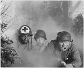 Movie still from 1951 film 'The Steel Helmet' a Korean War drama a medic a young Korean boy and a soldier peer ahead while on the ground