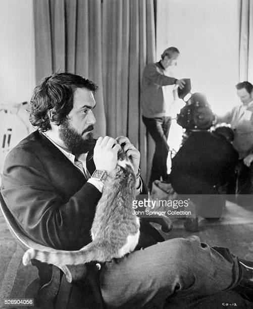 Movie still from A Clockwork Orange featuring Stanley Kubrick sitting in a chair playing with a cat