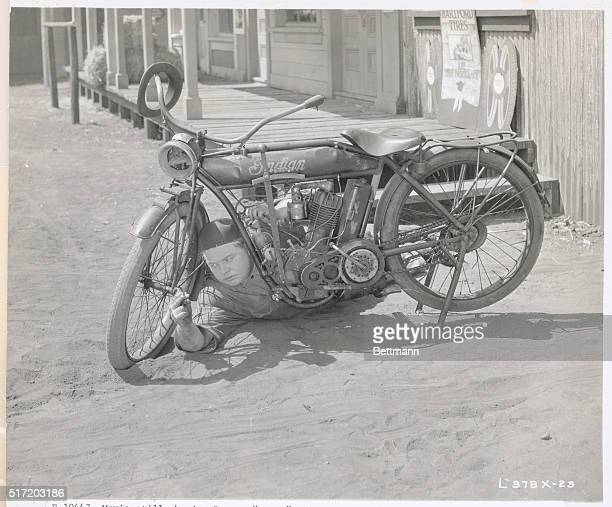Movie still showing Roscoe 'Fatty' Arbuckle slapstick comedian of silent film era repairing a motorcycle