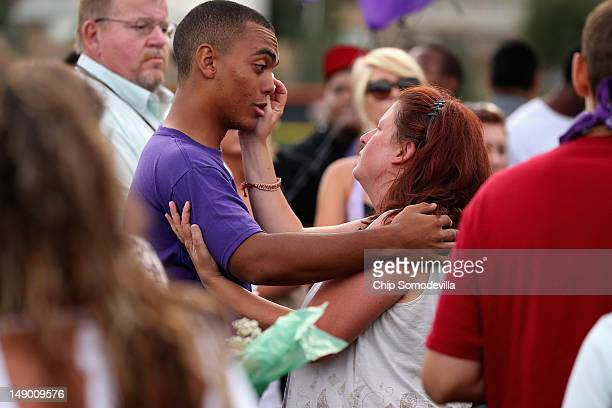 Movie theater shooting victim AJ Boik's mother wipes tears from the eyes of one of her son's friends as family friends and former classmates gather...