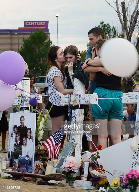 Movie theater shooting victim Gordon Cowden's daughters embrace at the makeshift memorial built across the street from the Century 16 theater July 23...