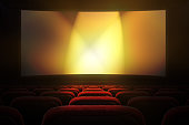 Movie theater with row of red seats and projection screen with golden lights in the background