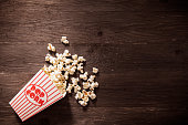 one box of popcorn on wood background ready for movie time overhead view
