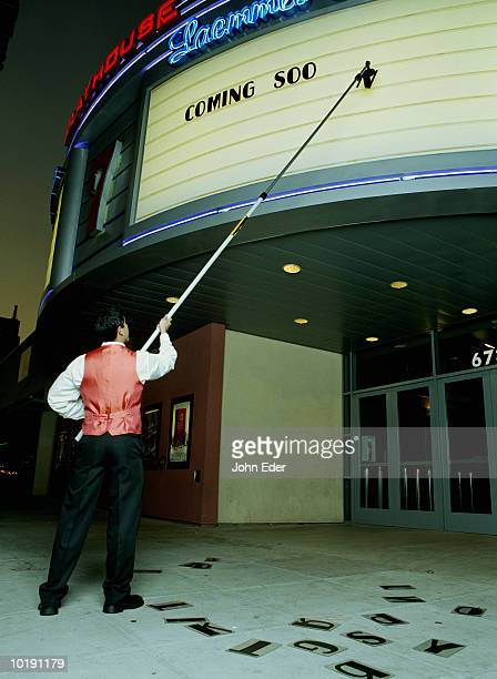 Movie usher putting up sign on marquee
