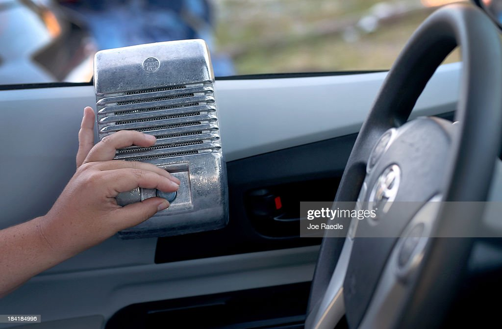 A moviegoer adjusts the volume on a car window speaker while waiting for the start of 'Back to the Future' at The Blue Starlite Mini Urban Drive-In on October 11, 2013 in Miami, Florida. Many traditional drive-in theaters around the United States have closed but the owner of The Blue Starlite held a grand opening for his small outdoor facility, which can accommodate 20 to 24 cars and has seats near the front of the viewing area, with hopes it will become popular in the urban core of Miami.