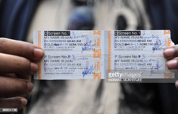 A moviegoer displays his ticket for the first screening of the day for 'My Name Is Khan' outside a city multiplex in Mumbai on February 12 2010...