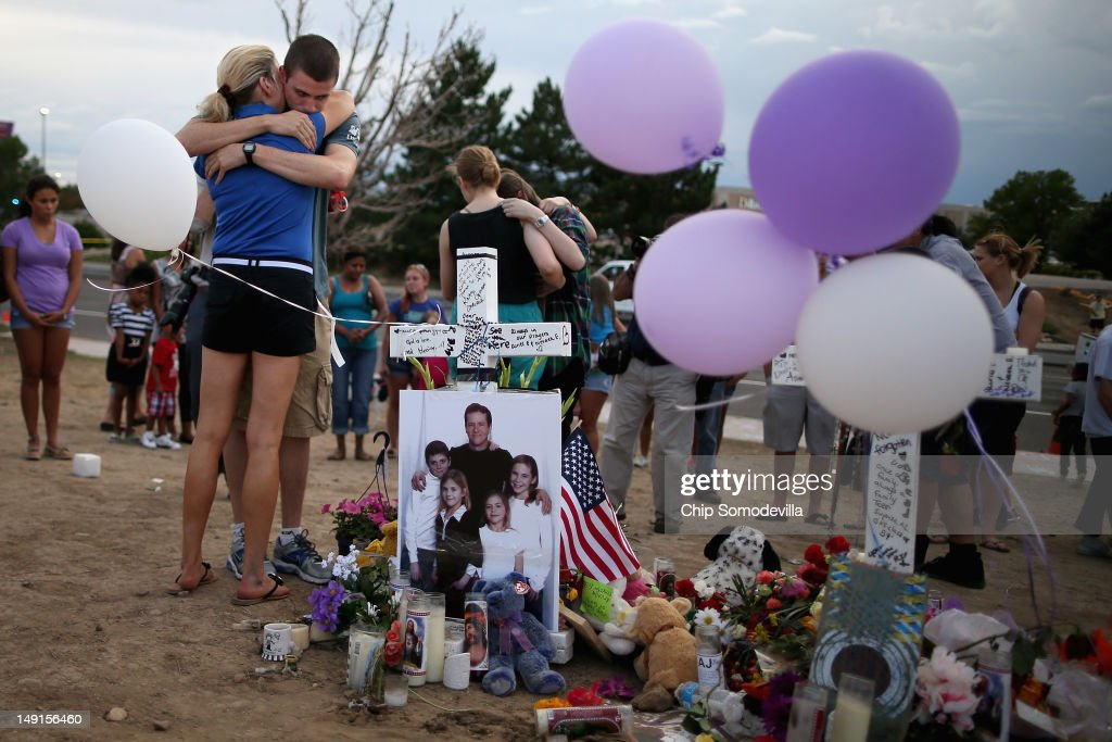 Movie-theater-shooting-victim Gordon Cowden's family gather at the makeshift memorial built across the street from the Century 16 theater July 23, 2012 in Aurora, Colorado. Two of Cowden's teenage daughters were with him in the theater when he was killed. Twenty-four-year-old James Holmes is suspected of killing 12 and injuring 58 others Friday during a shooting rampage at a screening of 'The Dark Knight Rises.'